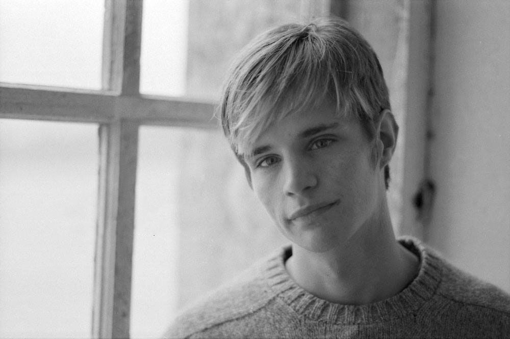 black and white photo of a young white male in his early 20s. he has blond hair that is combed over. He wears a sweater and stands in front of a large window.